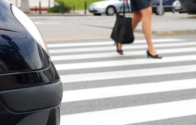 person crossing the street on crosswalk in front of a car