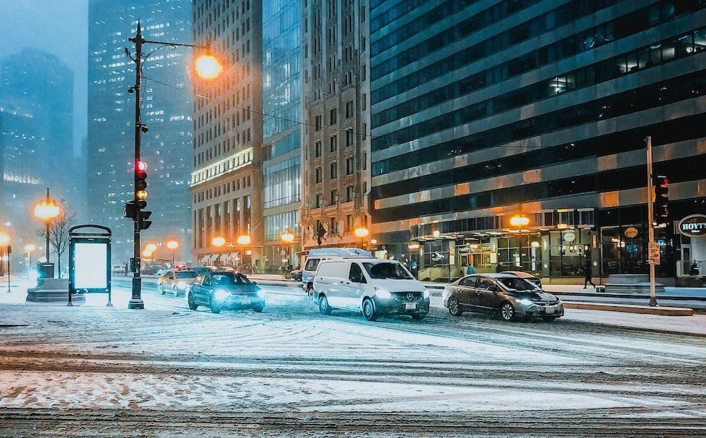 cars at traffic light in city with snow
